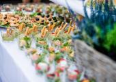 Przekąski cateringowe w małych kokilkach na stole z wrzosem